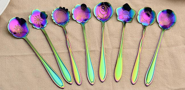 The set includes eight spoons each designed in a different flower shape, including a rose, pansy, and sunflower. 