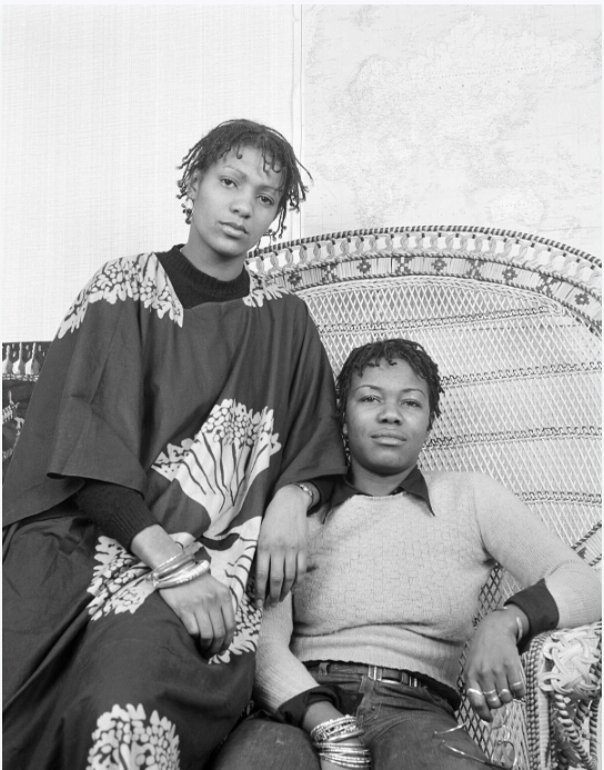 Anti-discrimination, women's and squatters' rights activist, Olive Morris (right) with friend Lia Obi posing in a Huey Newton style chair, used by the American Black Panthers. Olive's community work was recognised by Lambeth Council in 1986 when they named an office building Olive Morris House.