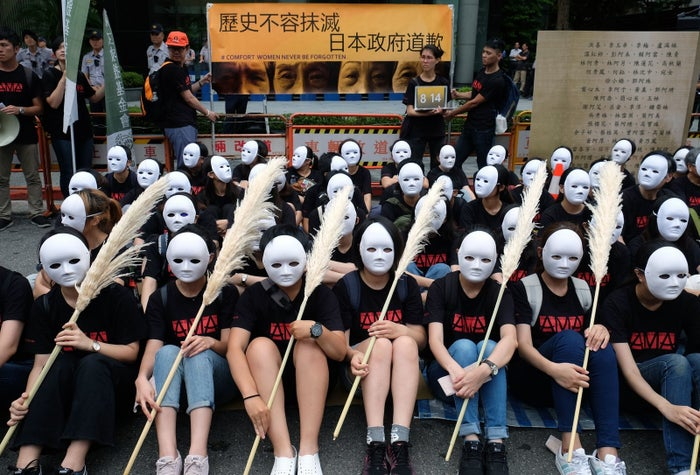 "Taiwanese NGO group members wear masks during a rally to demand that the Japanese government apologise to Taiwanese ""comfort women."""