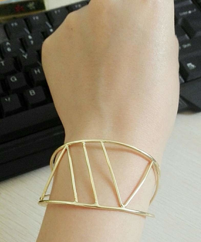 Model wearing the open cuff with thin metal shapes in gold