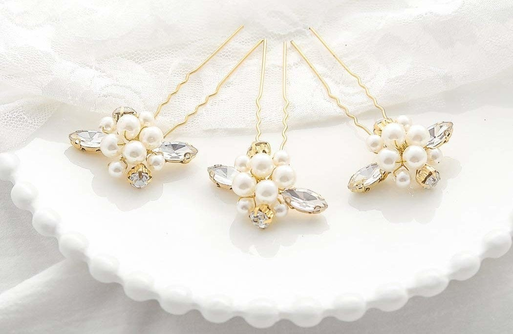 """Get a pack of three form Amazon for $7.66 (available in gold and silver, plus an all-rhinestone version for $7.66).Promising review: """"They are prettier, better made, and sturdier than I'd anticipated. Neither the pearls nor the gold look cheap or gaudy. They have some flexibility to bend as needed, to both stay in the hair and have the pearls arranged (clustered or not clustered) as you prefer. By having three pins, you can place them separately as desired, or group them together for impact. Great buy. Could not find what I wanted in any local store."""" —Avida Reader"""