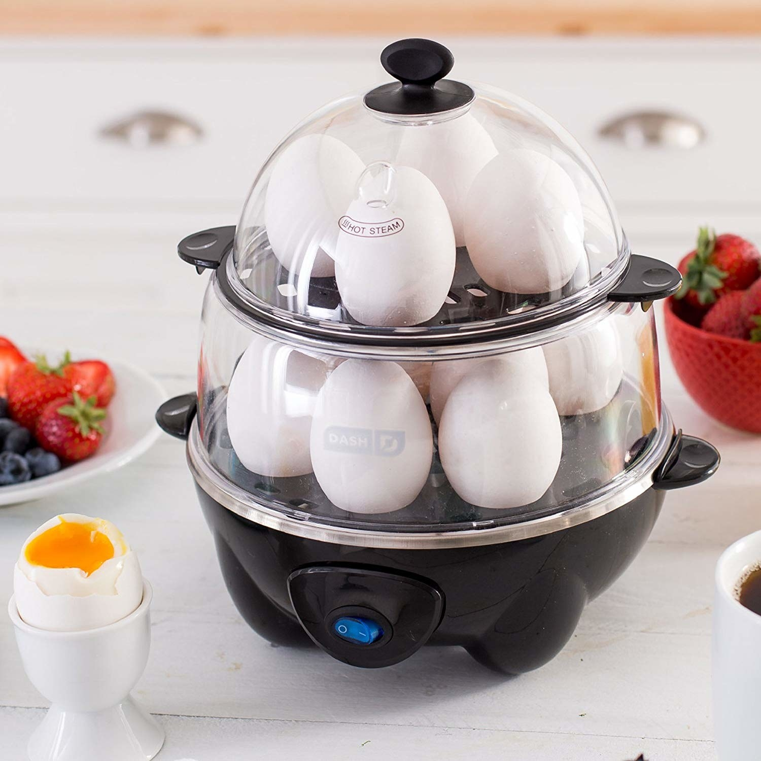 the egg cooker in black with a dozen eggs in it