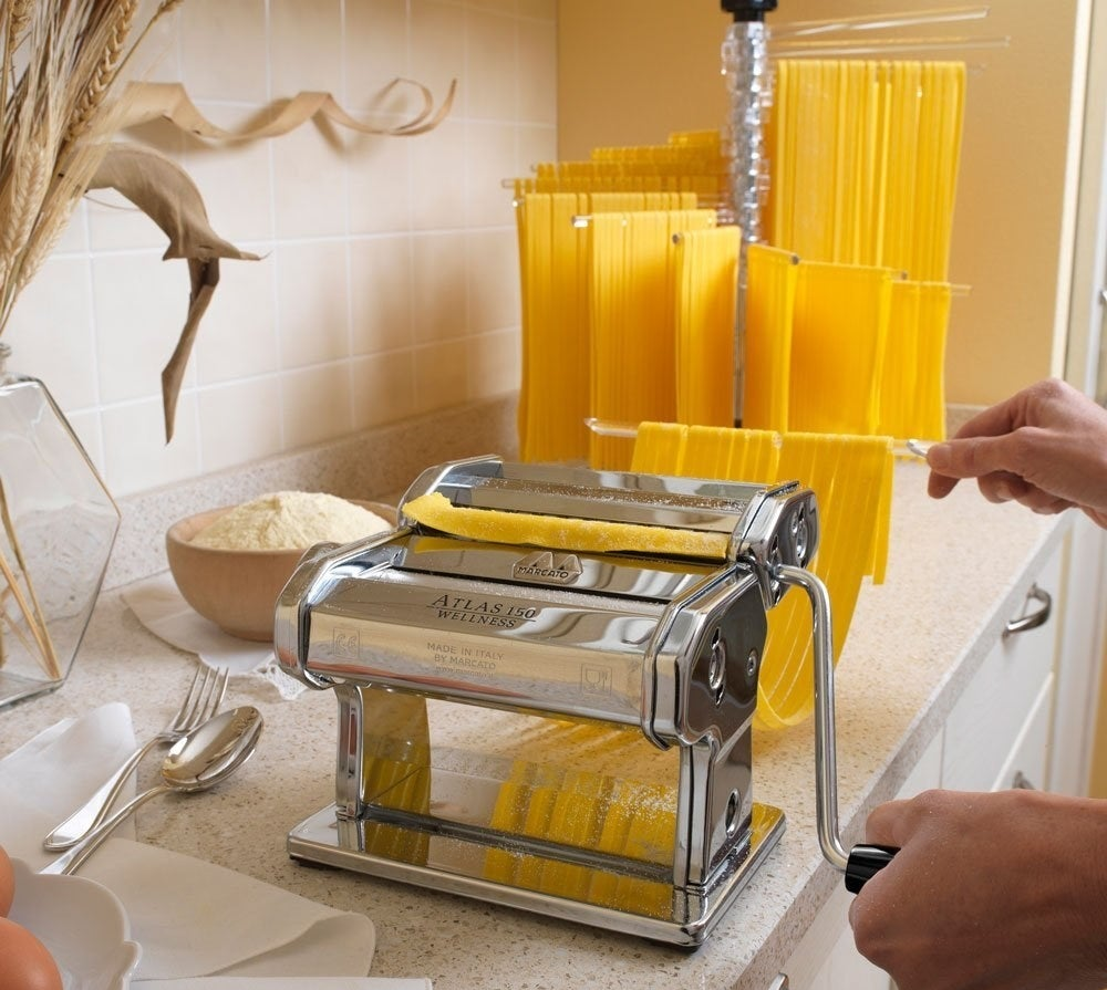 """This baby rolls and cuts pasta dough so you can make lasagna, fettuccine, and tagliolini. Includes the machine itself, a pasta cutter, a hand crank, and a clamp. Can make three pasta shapes, and is easy to attach additional (sold separately) accessories. To clean, simply wipe with a dry brush or cloth — NO WATER!Promising review: """"This thing is very high-quality. Follow the instructions and it works flawlessly. No doubt it will last a lifetime or three with proper care. In our kitchen, the mounting clamp is a little awkward but that's because our counters only hang a half inch past the cabinet but that's no fault of this machine. If yours are the same, you may need to be creative. We've made tons of pasta and ravioli with this thing. We bought the cheap ravioli trays and it's easy to make a gallon bag of ravioli and freeze the extras."""" —GO CHIEFS!Get it from Amazon for $78.95."""