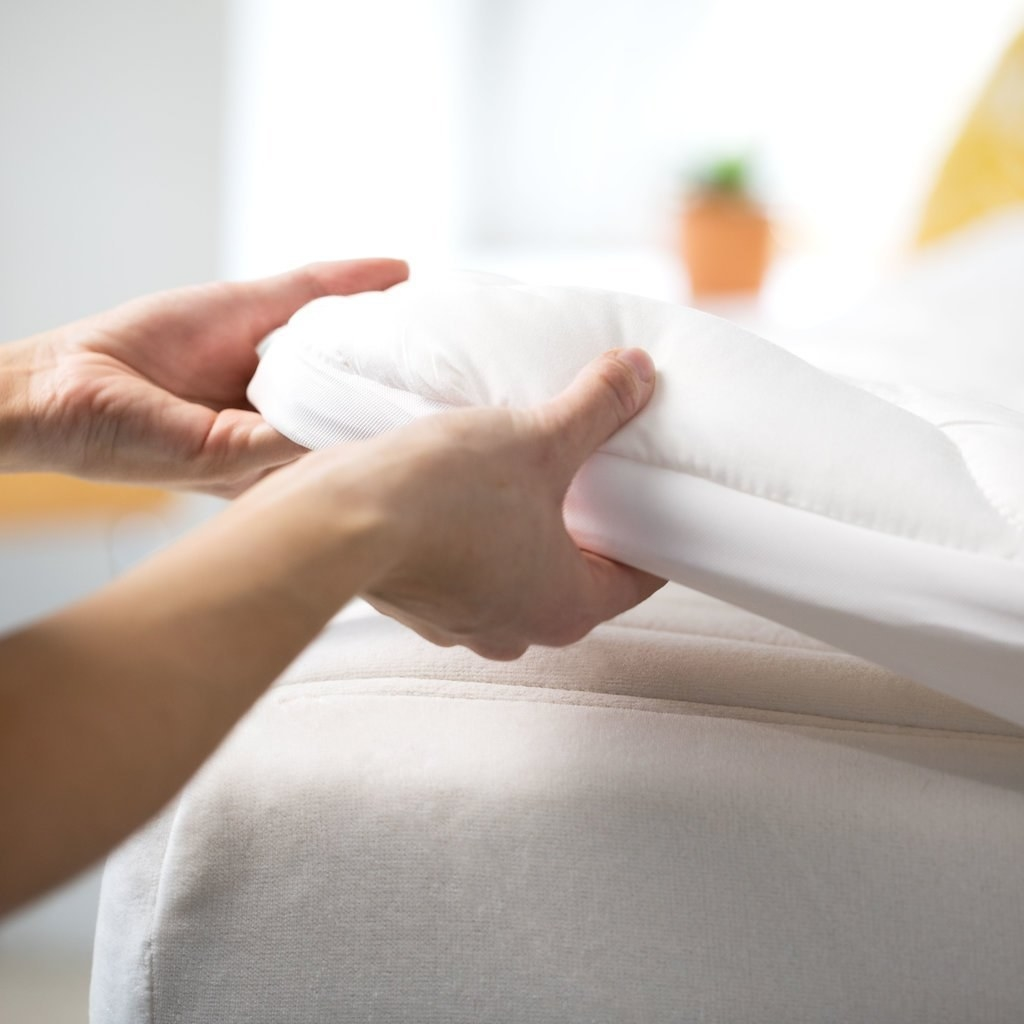 hands putting a fluffy mattress topper on a mattress