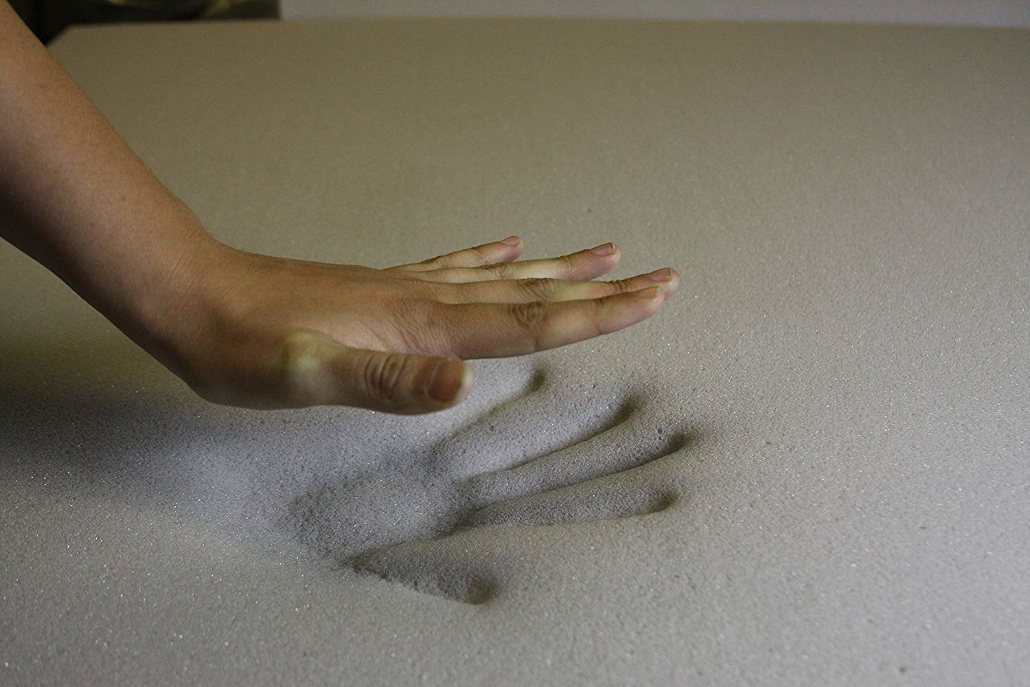 hand pressing into a memory foam pad topper on mattress
