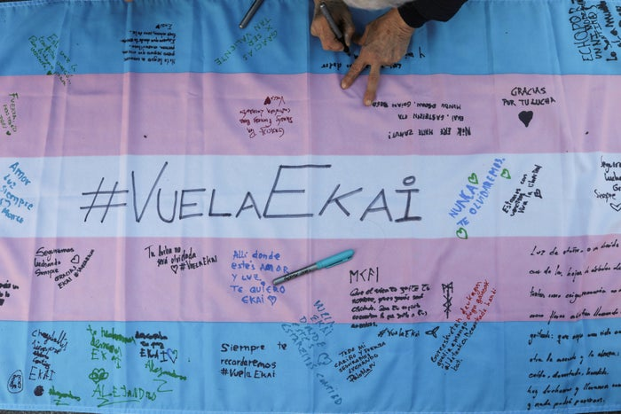 People write messages on a transgender flag during a gathering to remember 16-year-old transgender boy Ekai, who killed himself, in Madrid.