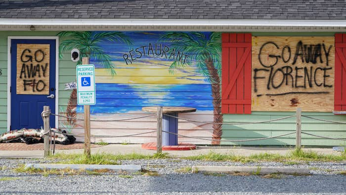 Spray-painted signs on a boarded-up building before Hurricane Florence comes ashore on Oak Island, North Carolina.