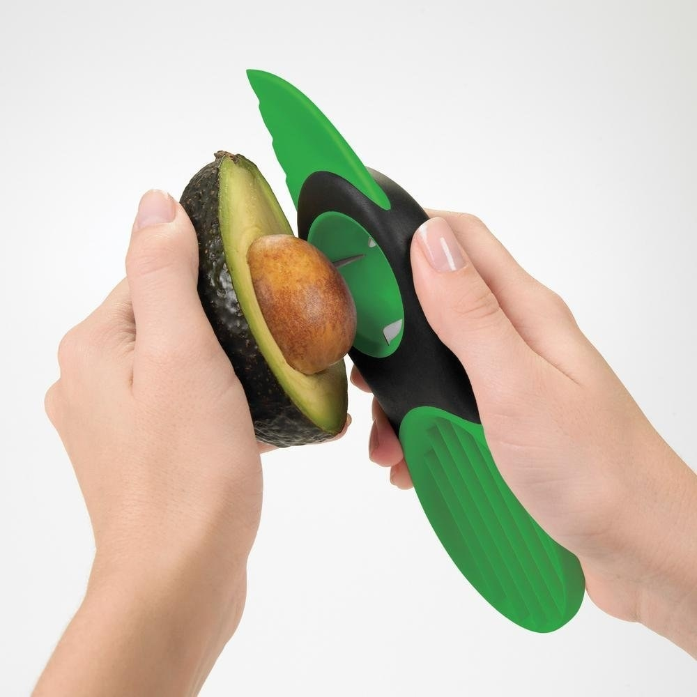 Hands using the three-in-one tool to pit an avocado