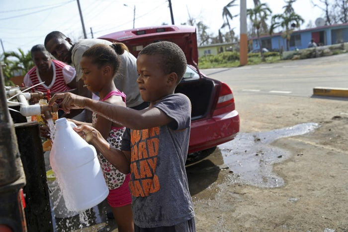 Children fill up bottles with water at a water distribution point in the aftermath of Hurricane Maria on Sept. 24, 2017.