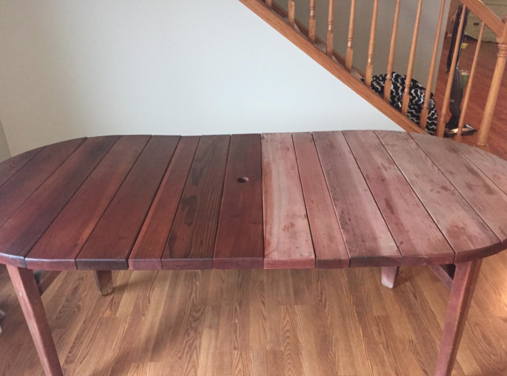 a dining room table with half of its wood faded and the other half treated with the wood conditioner