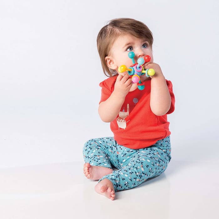 """Promising review: """"This is a perfect toy for my 3-month-old! It is small enough for her to hold on to, and she loves the light rattle sound and the bright colors. Since I bought it two weeks ago, it has helped her learn how to intentionally grab onto things. And she can chew on it without gagging, which I love. I attached a pacifier clip so it doesn't fall on the ground. It's definitely a favorite toy in our house. I'm so glad I bought it!"""" —alm2013Get it from Amazon for $8.99."""