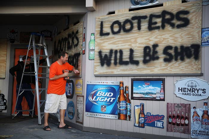Residents of Myrtle Beach, South Carolina, use plywood with the words 'Looters will be shot' to cover the windows of a bar ahead of the arrival of Hurricane Florence on Sept. 12.