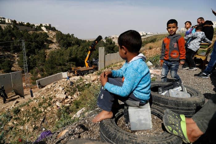 東エルサレムにあるシュアファト難民キャンプで、分離壁の崩壊した箇所を交換するイスラエル軍と、それを眺めるパレスチナ人の子どもたち。