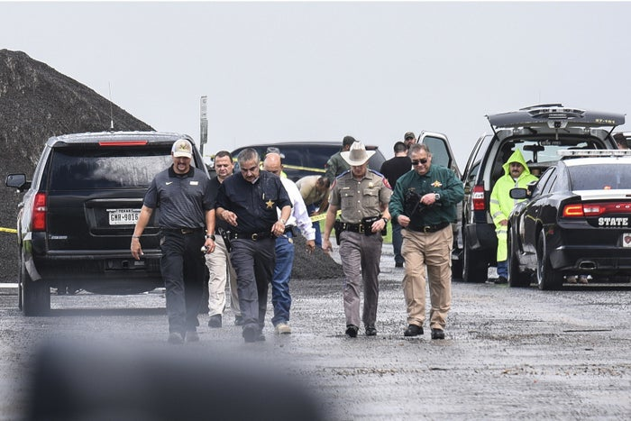 Law enforcement officers gather near the scene where the body of a woman was found near Interstate 35 north of Laredo, Texas, on Saturday.