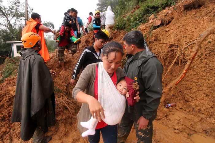 Families and relatives of miners move to safer ground after massive landslides triggered by Mangkhut in Itogon town, Benguet province, in the Philippines.