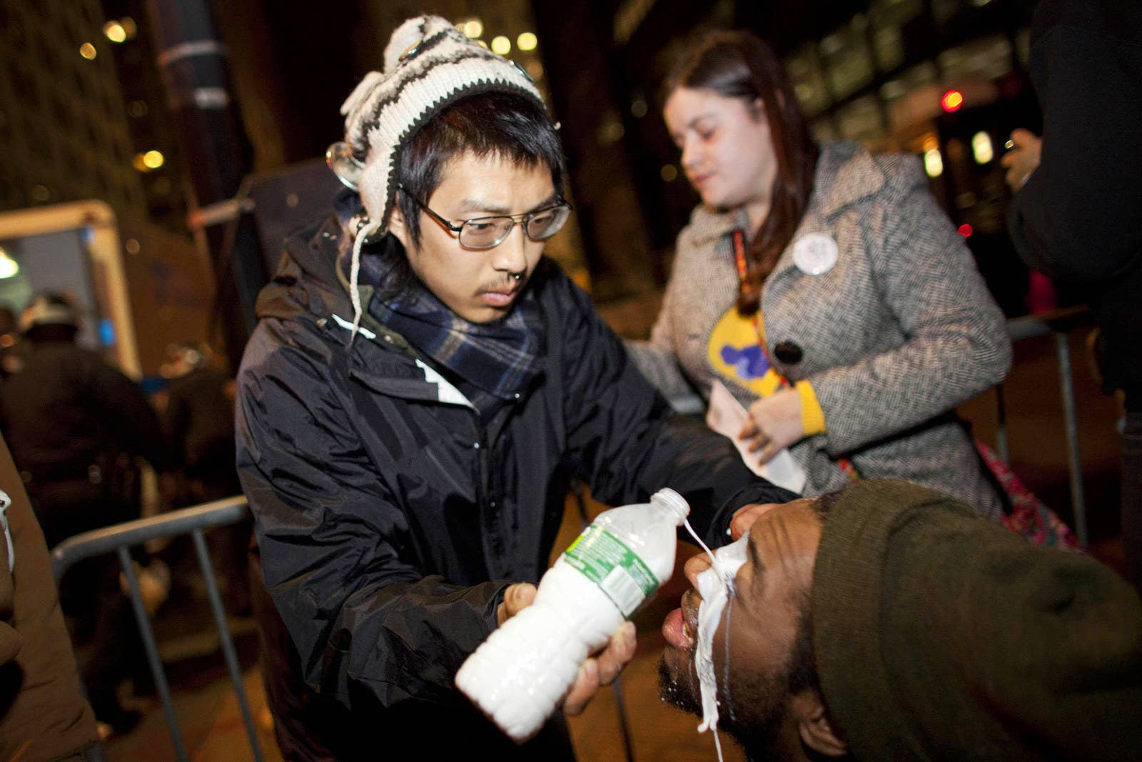 A protester pours liquid over the eyes of another protester to ease the pain from pepper spray during an unannounced raid by the New York City Police Department on Zuccotti Park during the early hours of Nov. 15, 2011.