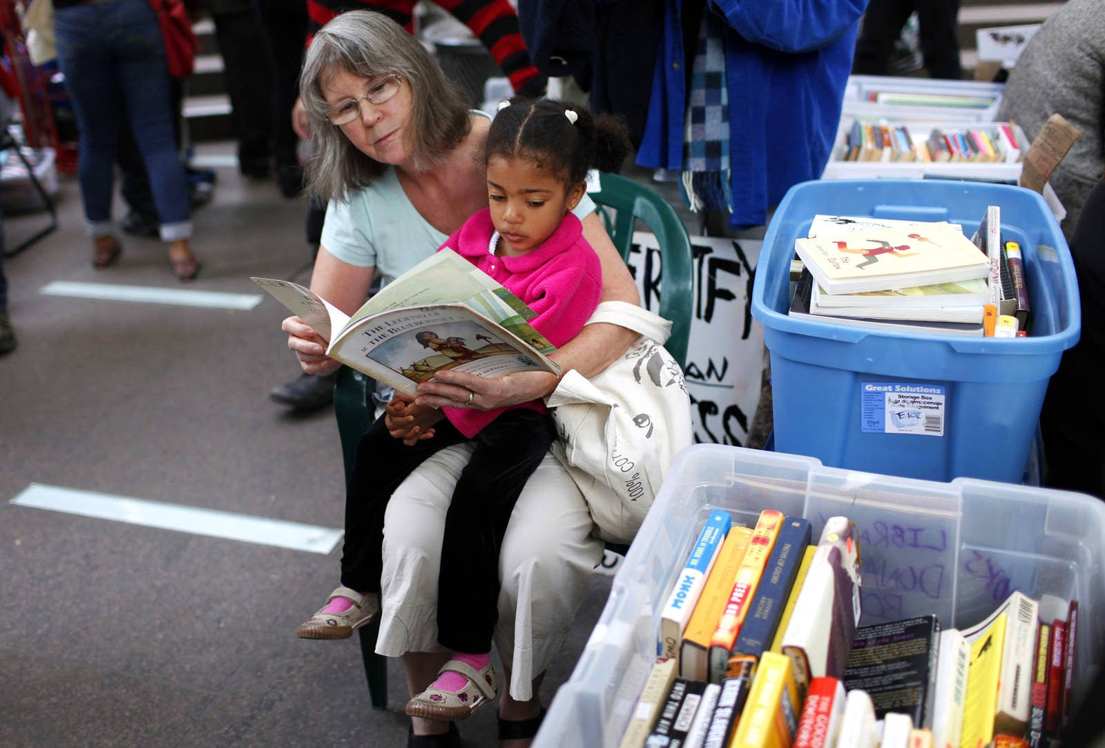 A woman reads to a child at a makeshift library in Zuccotti Park on Oct. 18, 2011.