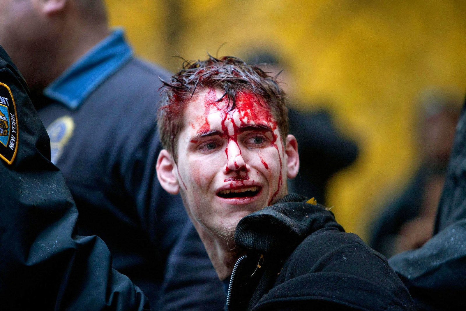 A man is seen with blood on his face after being apprehended by police in Zuccotti Park on Nov. 17, 2011.
