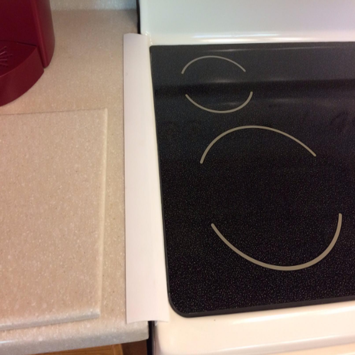 The narrow cover placed between a countertop and stovetop, covering the gap
