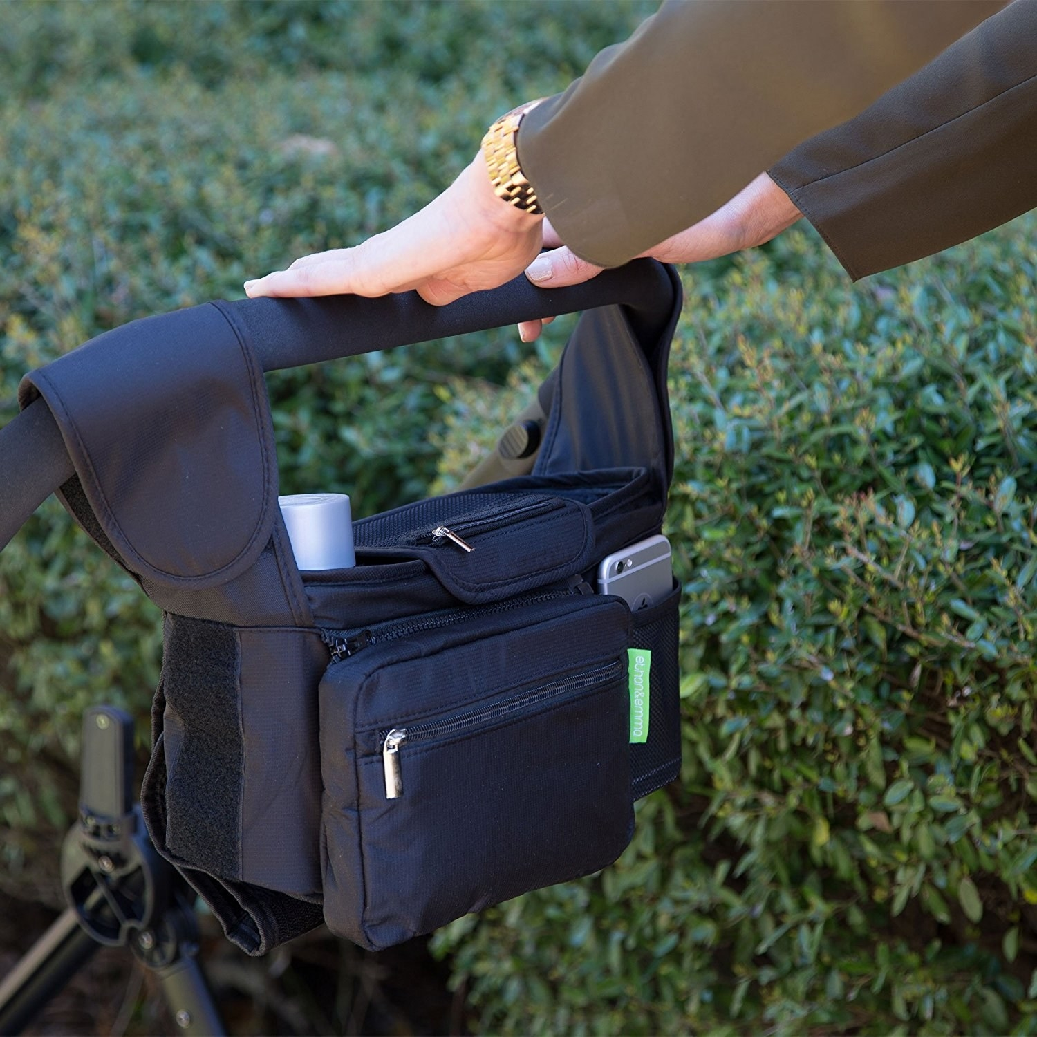 Person pushing stroller with storage bag hanging on handle