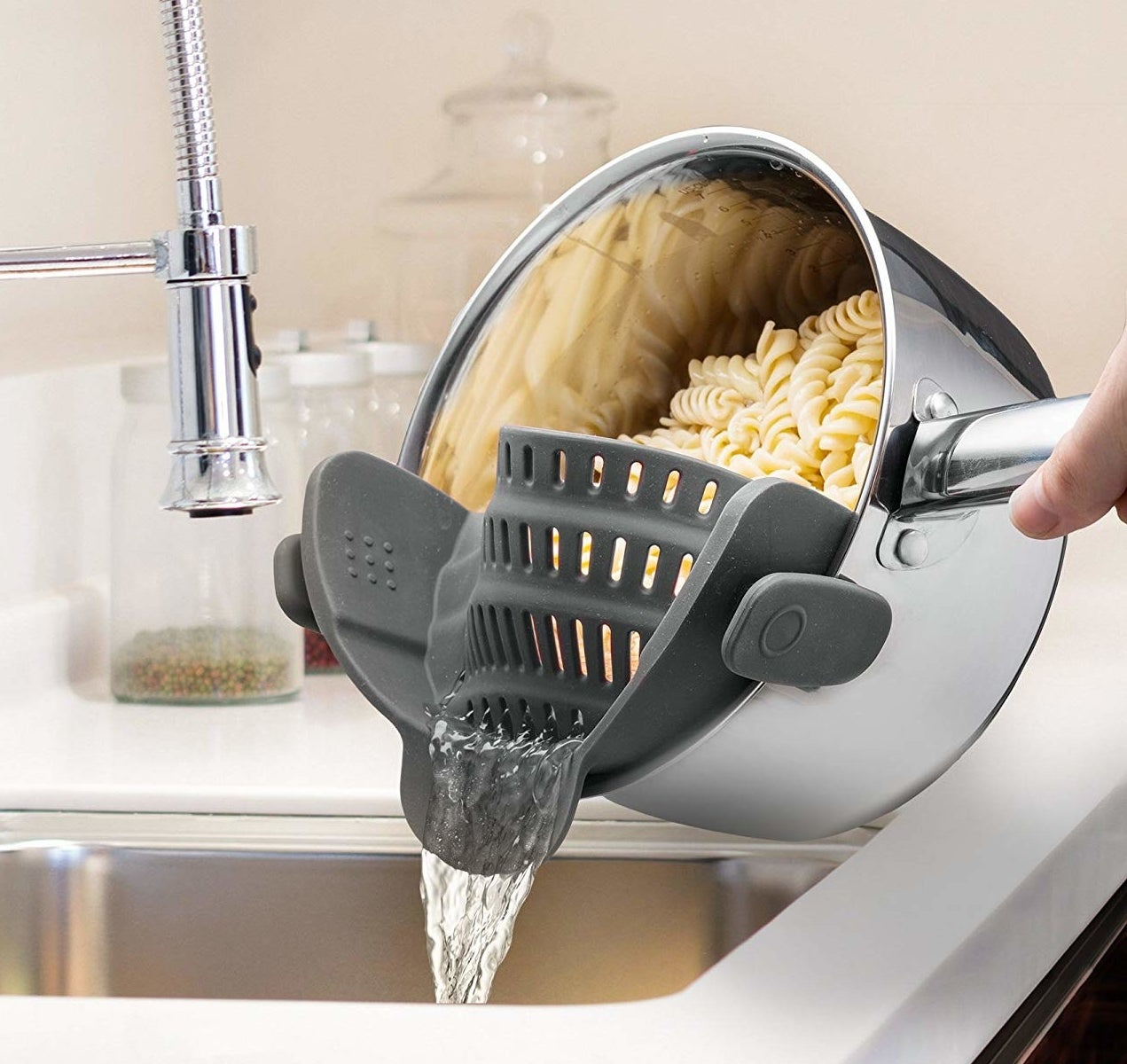 The strainer attached to a pot, which allows the water to drain while keeping pasta in place