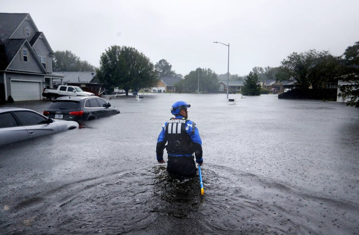 A member of the North Carolina Task Force urban search and rescue team wades through a flooded neighborhood looking for residents who stayed behind in Fayetteville, North Carolina, on Sept. 16.