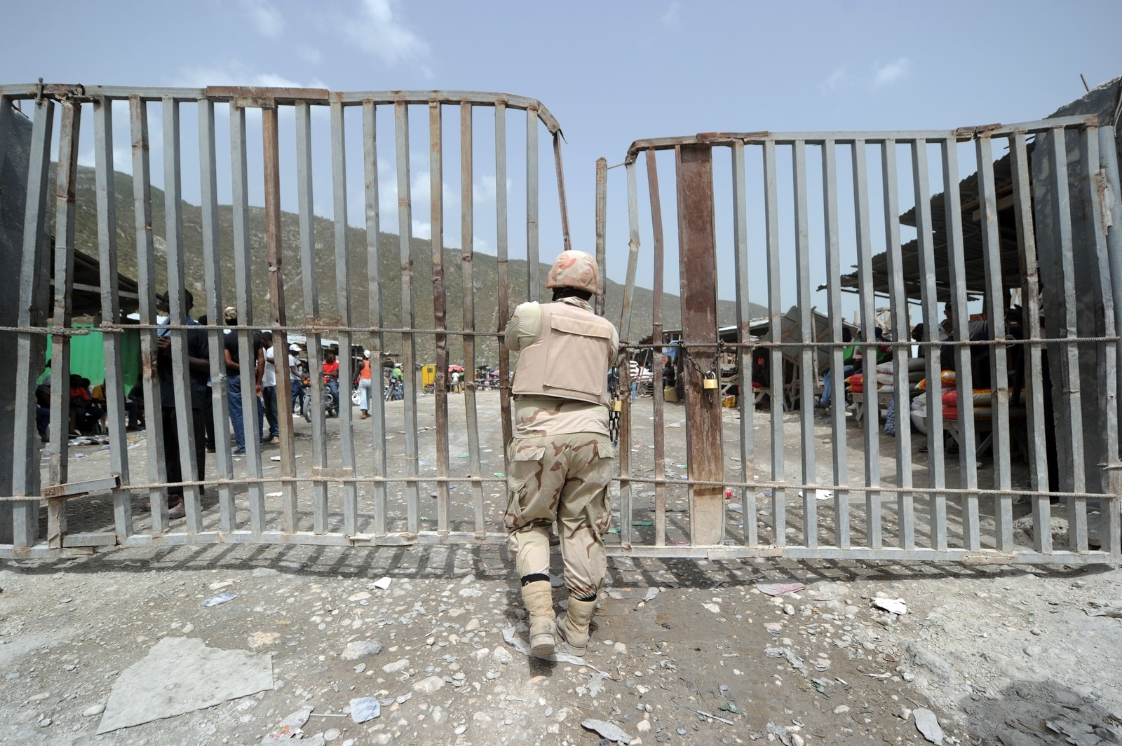 A Dominican soldier closes the gate at the border.