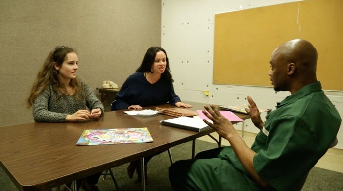 Georgetown University students Julie Fragonas and Isobella Goonetillake speak with Valentino Dixon at Wende Correctional Facility.
