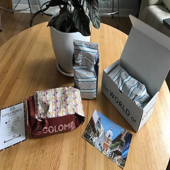 the box with a pack of Colombian coffee and a postcard