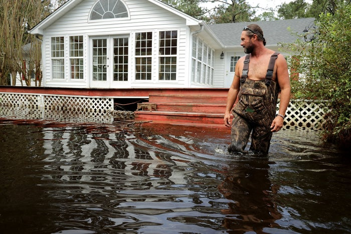 A man wades through about three feet of floodwater at his father's home in Kinston, North Carolina.