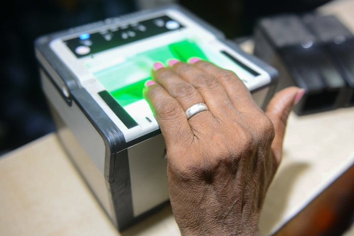 An Indian woman gets her fingerprints read during the registration process for Aadhaar.