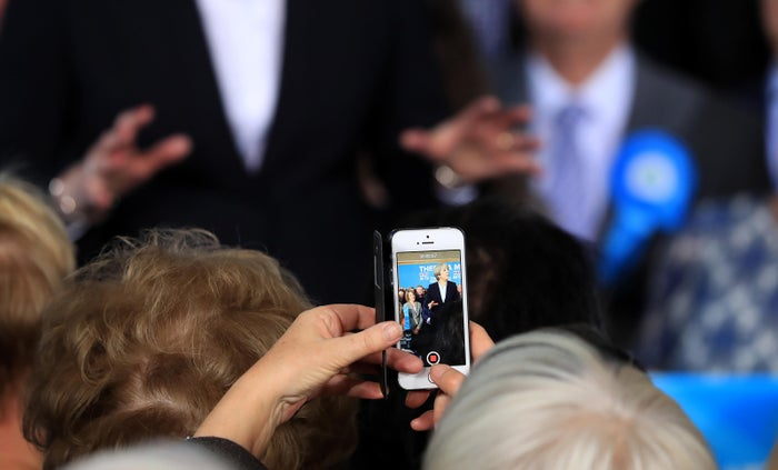 British Prime Minister Theresa May is seen on a mobile phone while delivering a speech to Conservative party supporters in Mawdesley Village Hall.