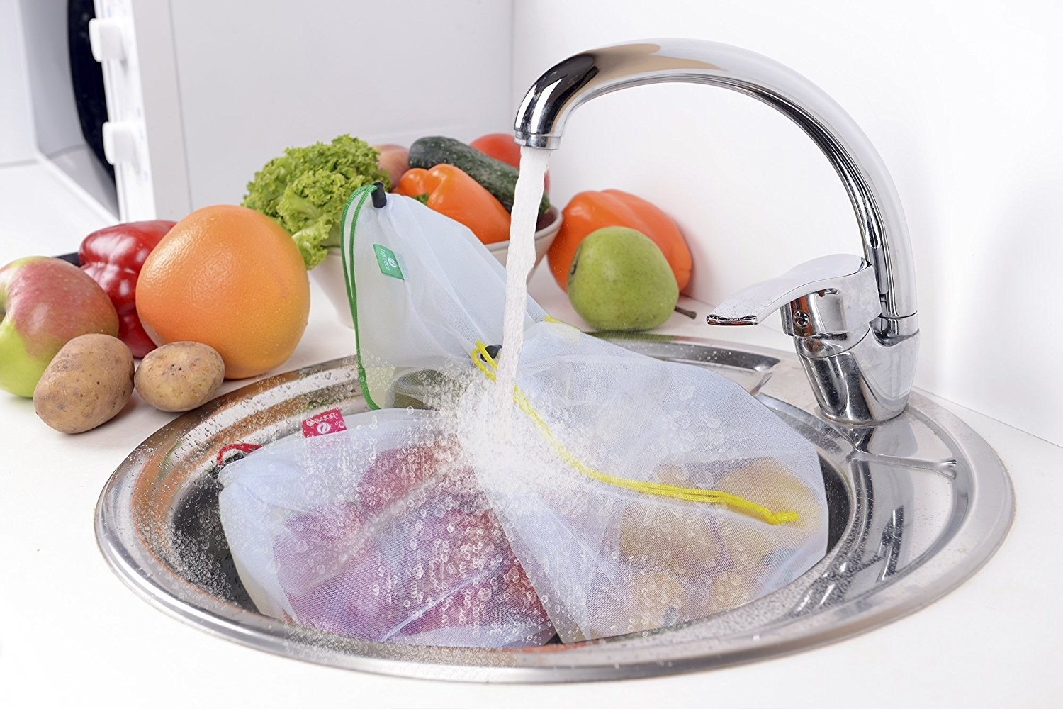 The bags filled with produce being rinsed in a sink