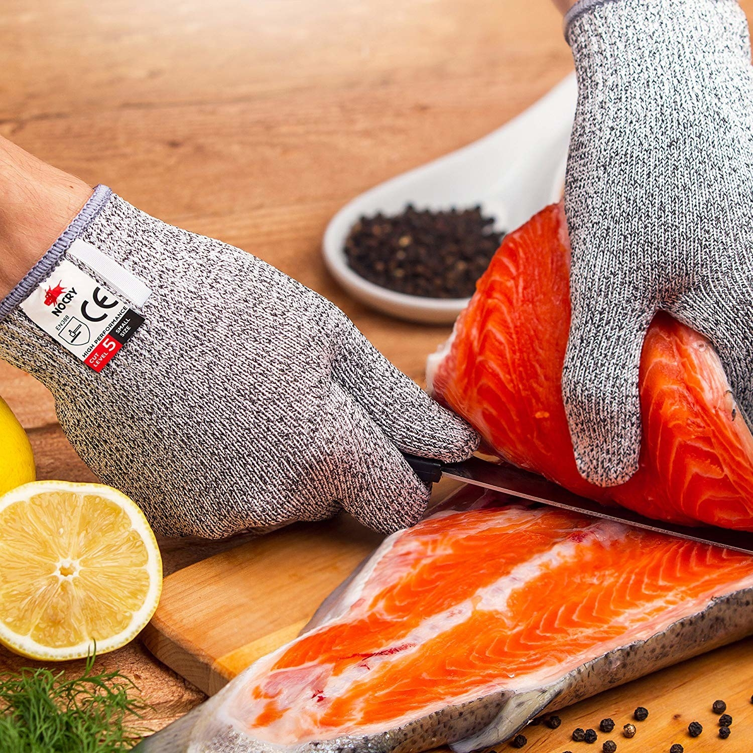 A person wearing the gloves while cutting fish