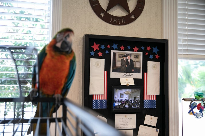 A framed photograph of Anwar Khalifa with former President George W. Bush shares space with Kiwi, Khalifa's pet macaw, in his office.