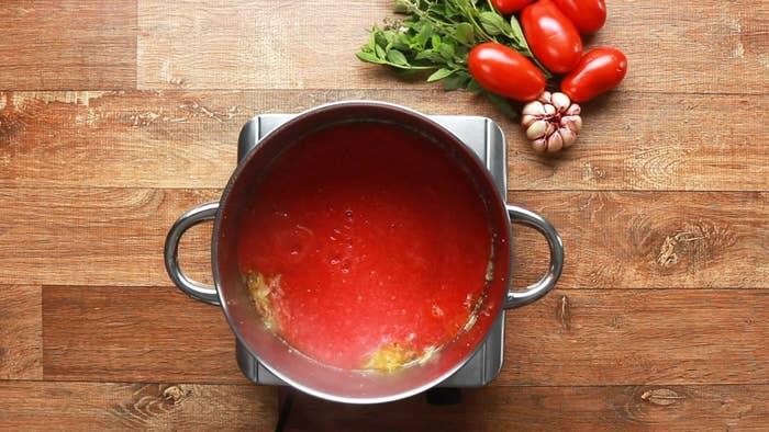 Molho fácil de tomateRendimento: 6 xícarasVocê vai precisar de:1,5 kg tomate italiano maduro cortado3 colheres de sopa de azeite1 cebola pequena fatiada finamente2 dentes de alho ralados1 ramo de manjericãoSal a gostoPimenta do reino a gostoModo de preparo:1. Retire as hastes dos tomates, depois use uma faca pequena e afiada para cortar o olho do tomate (onde o caule encontra a fruta). Corte em cubos grandes e adicione ao liquidificador. Bata até ficar homogêneo.2. Aqueça o azeite em uma panela grande em fogo baixo, junte a cebola e o alho e refogue, por cerca de 2 minutos, até ficar translúcido e levemente dourado.3. Adicione o purê de tomate e deixe cozinhar por cerca de 1 hora, até que o molho seja reduzido em ⅔.4. Desligue o fogo e adicione o manjericão, sal e pimenta. Deixe esfriar por alguns minutos.5. Use imediatamente ou coloque o molho em sacos com fecho hermético, alise e congele até 3 meses.6. Aproveite!