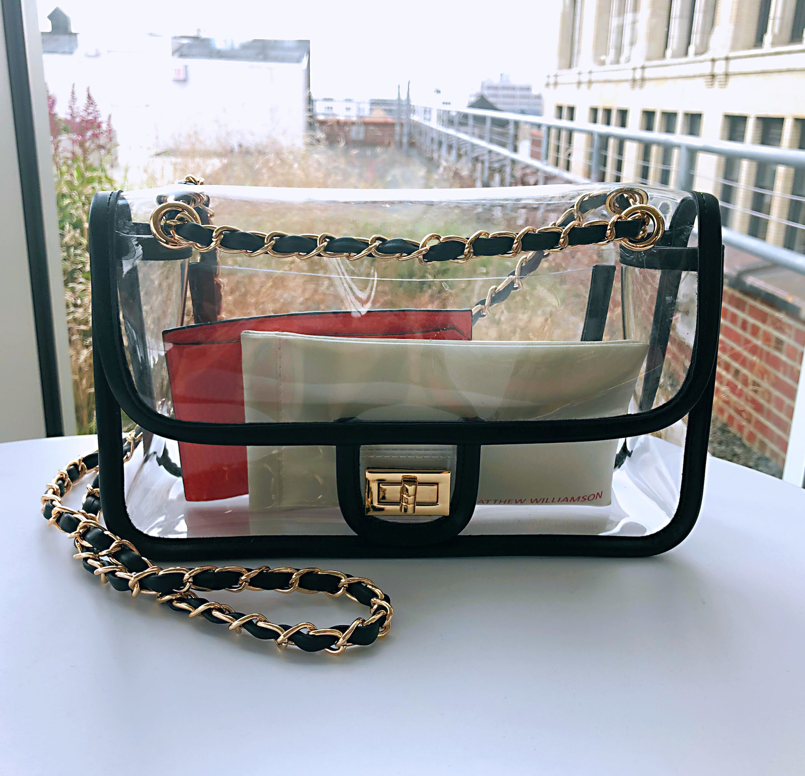 The clear plastic, black trimmed chain strap bag with a gold chain strap and turnlock with wallets inside. It's shaped like a classic Chanel bag