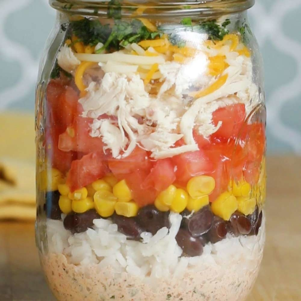 a mason jar filled with rice, beans, corn, tomato, and chicken