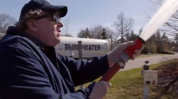 Michael Moore spraying the Michigan governor's lawn with water.
