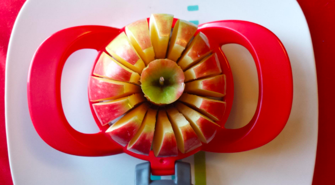 an apple being sliced into 16 even slices with the cutter