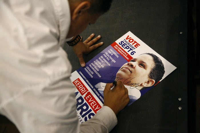 Kerri Evelyn Harris autographs a campaign poster after a town hall on Aug. 31 at the University of Delaware.