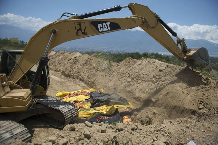 An excavator is used to bury quake victims in a mass grave in Palu, in Central Sulawesi.