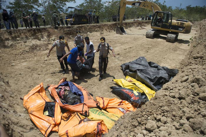 Officials carry body bags into a mass grave ahead of a mass funeral for quake victims in Palu, in Central Sulawesi.