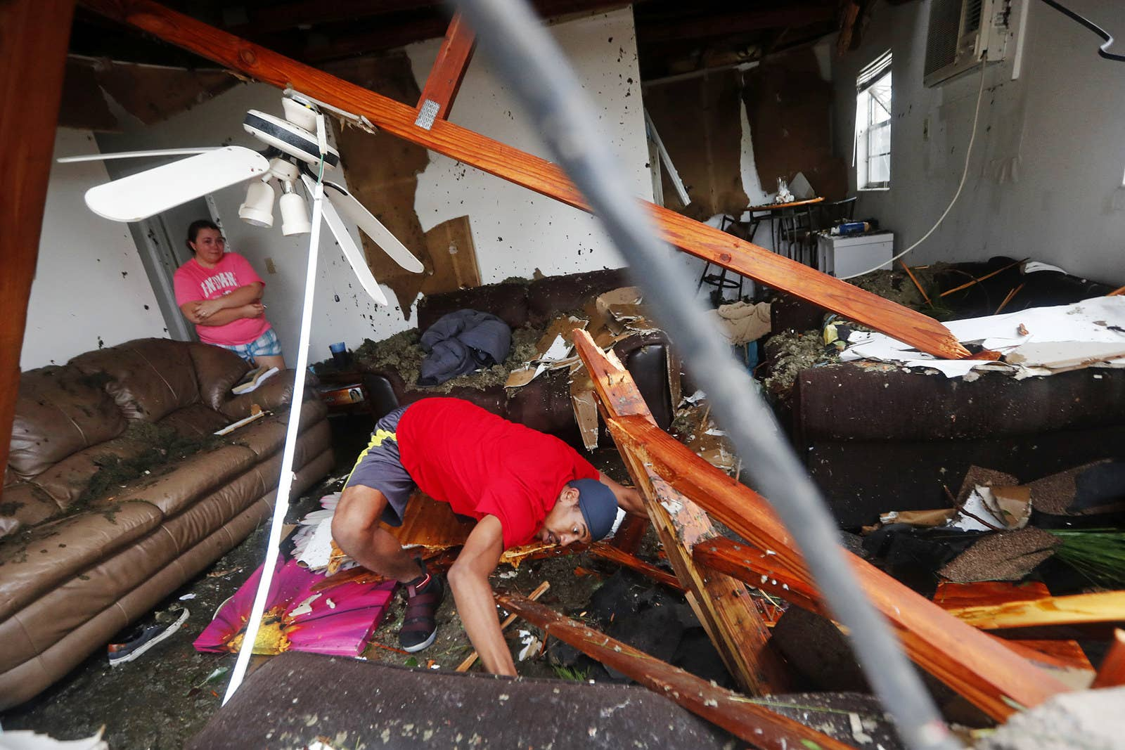 Dorian Carter looks under furniture for a missing cat after several trees fell on a home in Panama City, Florida.