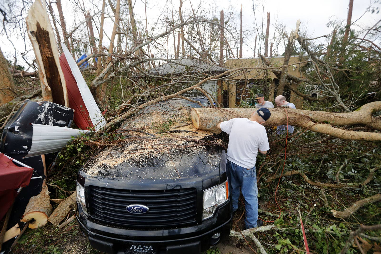 People cut away a tree that landed on a vehicle in Panama City, Florida.