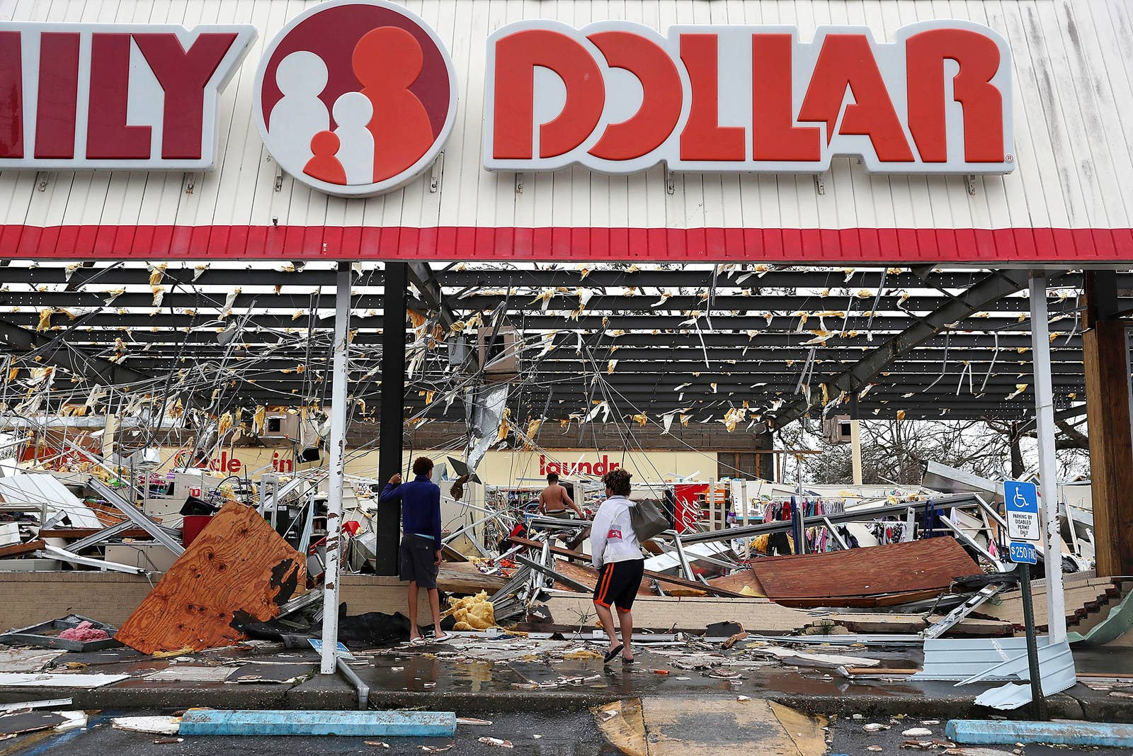People look on at a damaged store after Hurricane Michael passed through Panama City, Florida.