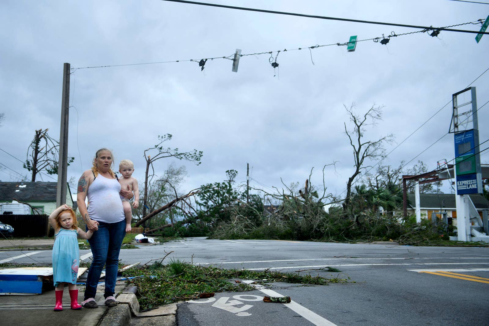 A woman and her children wait near a destroyed gas station in Panama City, Florida.