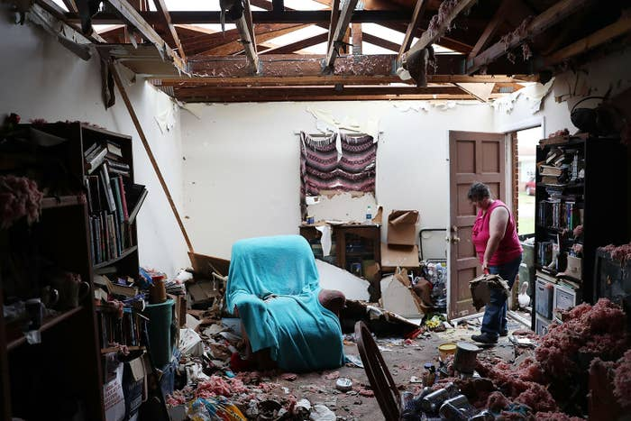 Amanda Logsdon begins the process of trying to clean up her home after its roof was blown off by Hurricane Michael's winds on Oct. 11, in Panama City, Florida.