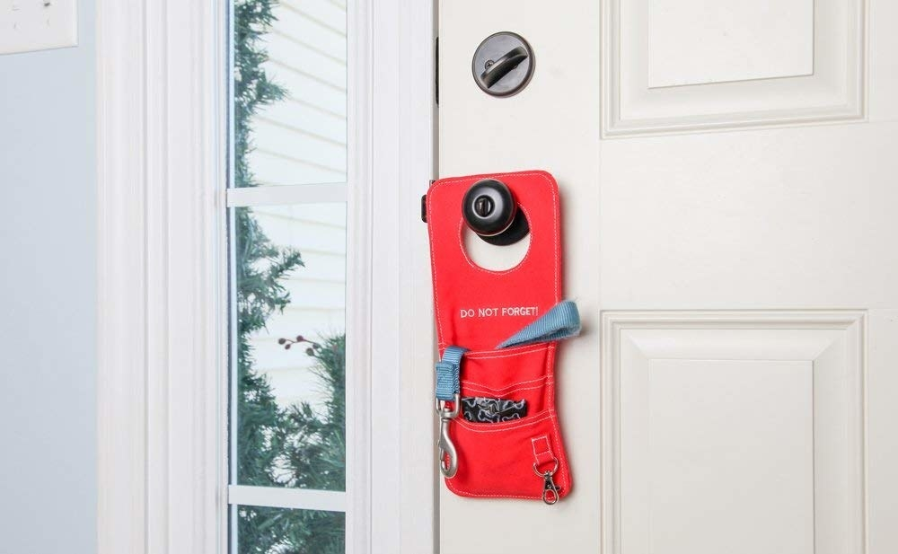 the red door organizer hanging from a door knob outside of someone's home