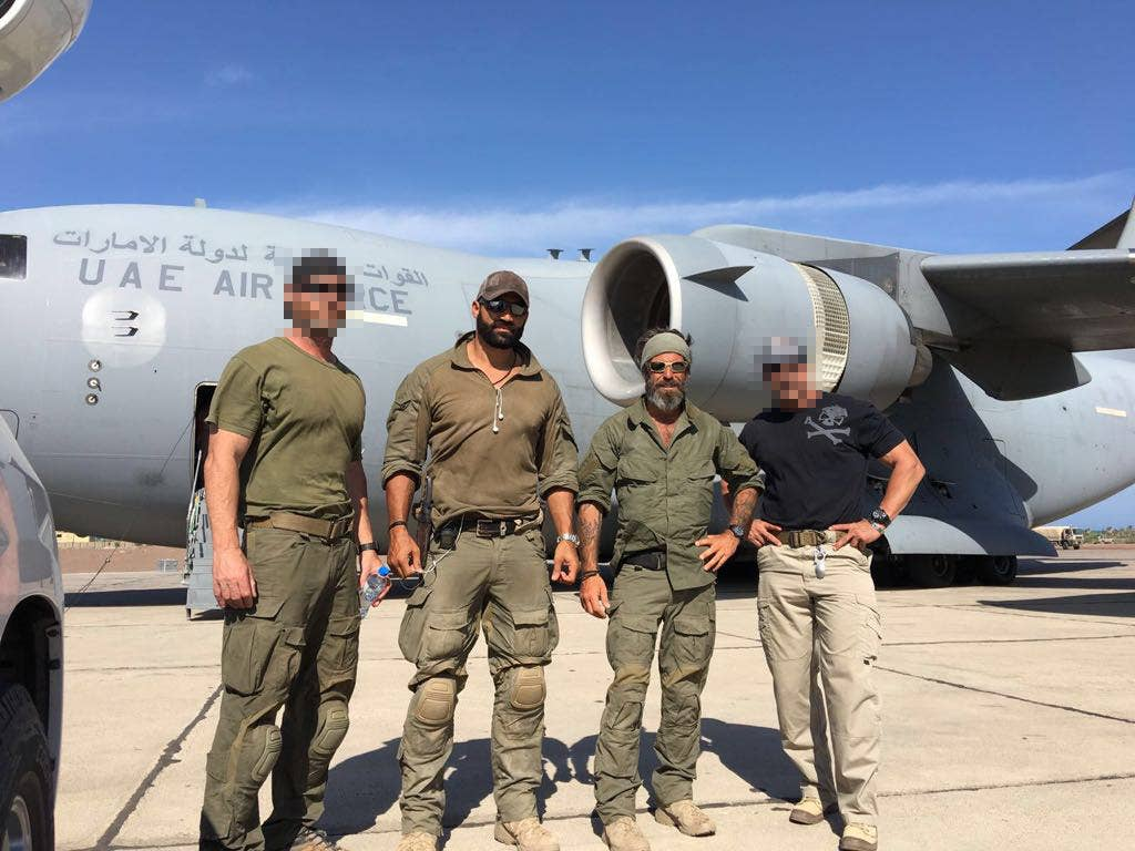 Standing in front of a UAE military plane are Gilmore (middle left), Golan (middle right), and two soldiers on their mercenary team.
